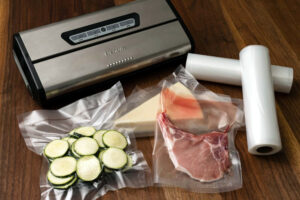 Vacuum_sealer_with_food_sealed_on_wooden_table_and_rolls_of_plastic_for_sealing